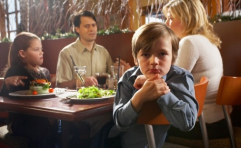Bored boy at table in restaurant with others